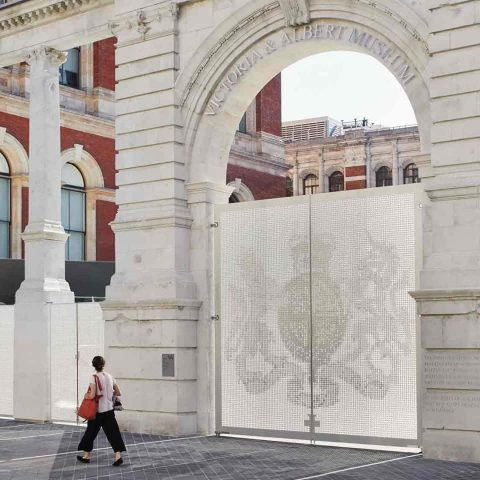 Central aluminium gates at the V&A Museum with lady walking by and looking